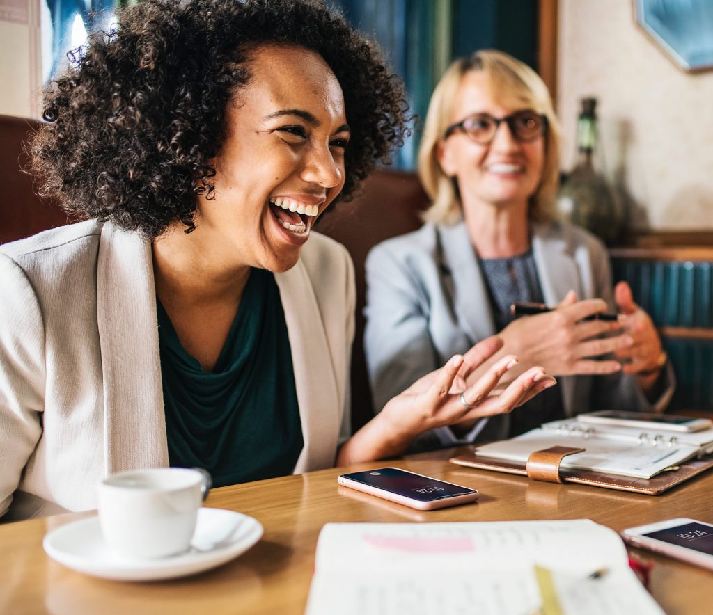Two women laughing and smiling during workplace mentoring session.