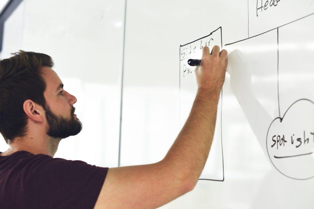 Breaded man is drawing on a whiteboard.