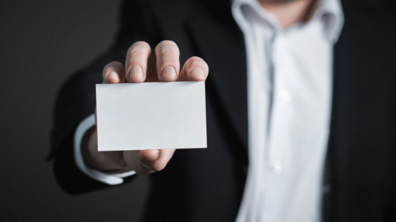 A man in a suit holds up his business card to the camera, but his business card is blank.
