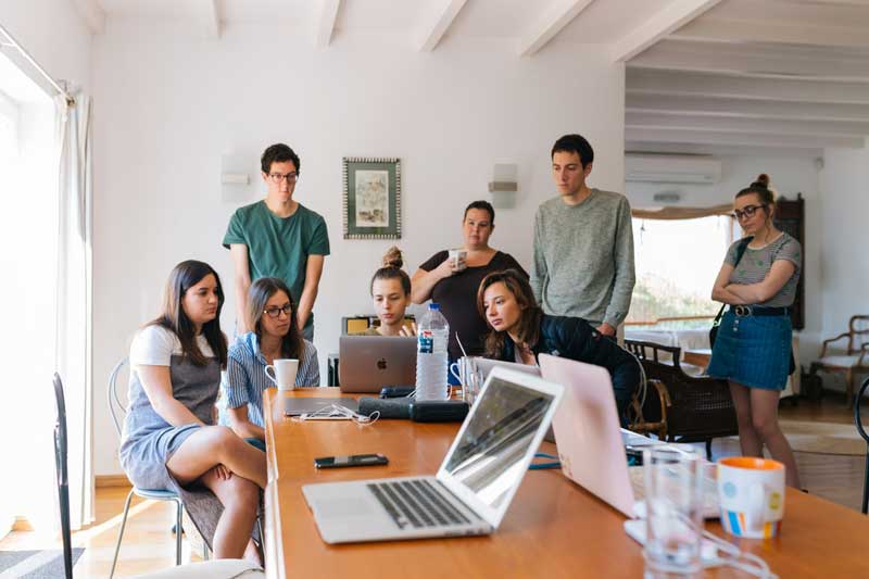 Group of millennial employees sit around a computer in an open plan office space.
