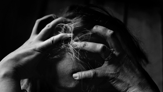 A woman is scrunching her hands in her hair.