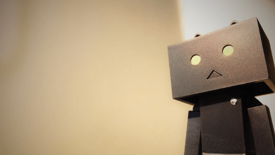 A robot stands in the light of the sun.