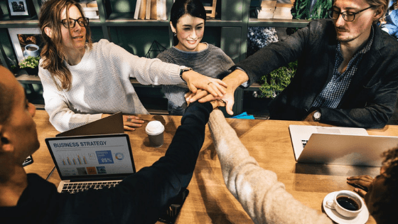 a group of employees put their hands in the middle to celebrate their team work. They are all smiling and happy in their positive company culture.