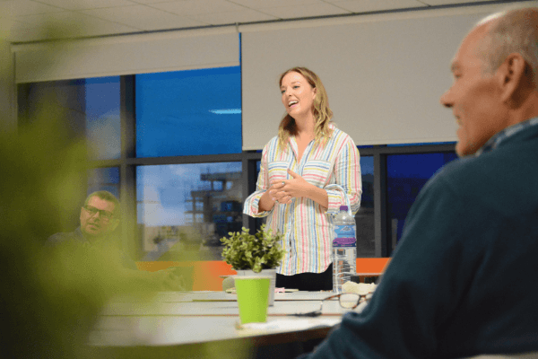 A photo of Lizzie Benton, Founder of Liberty Mind. She is standing in front of people during a company culture workshop listening to people talk.
