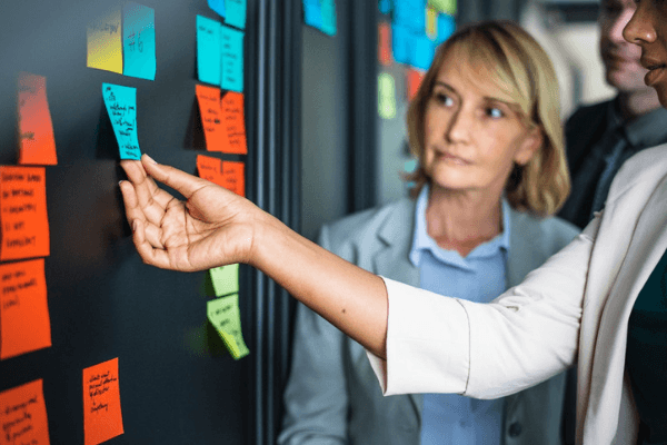 A woman is pulling sticky notes off a wall and talking to her colleague.