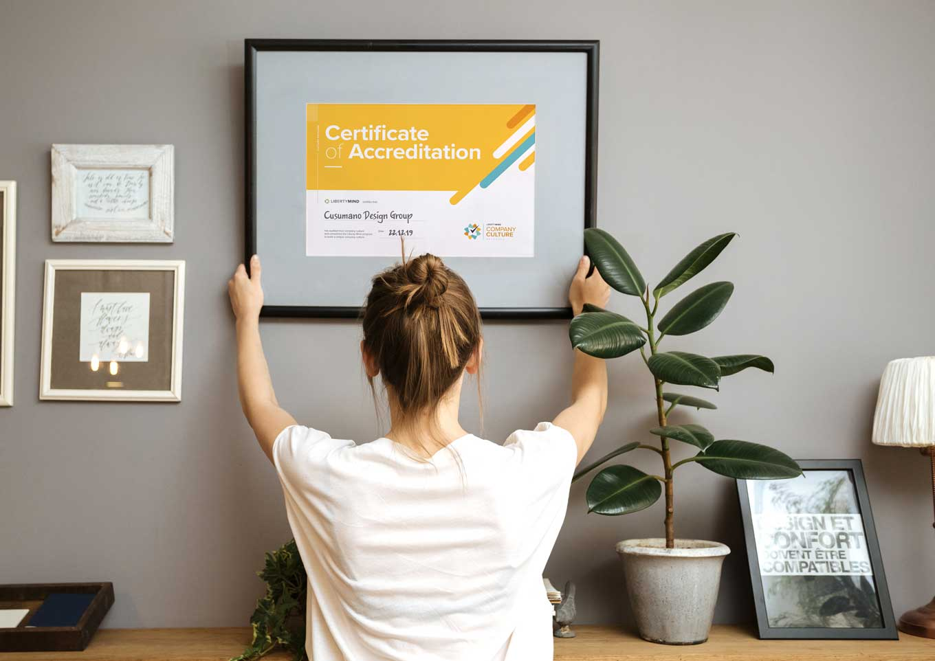 Woman putting up her Liberty Mind Company Culture Certificate on the wall of her office.