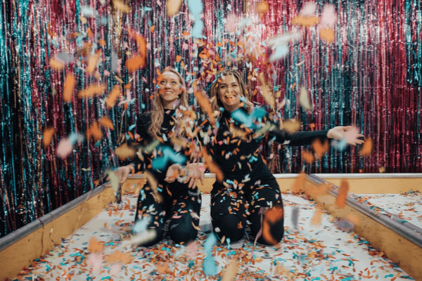 Two women stand in a party room throwing paper confetti.