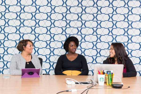 Three woman sit at a desk talking in a meeting room. Two of them have their laptops in front of them.