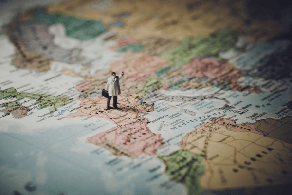 A figurine of a map stood on the world map holding his hand up in the air.