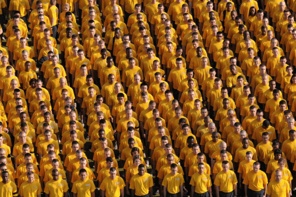 Hundreds of people are all lined up wearing a yellow tshirt.