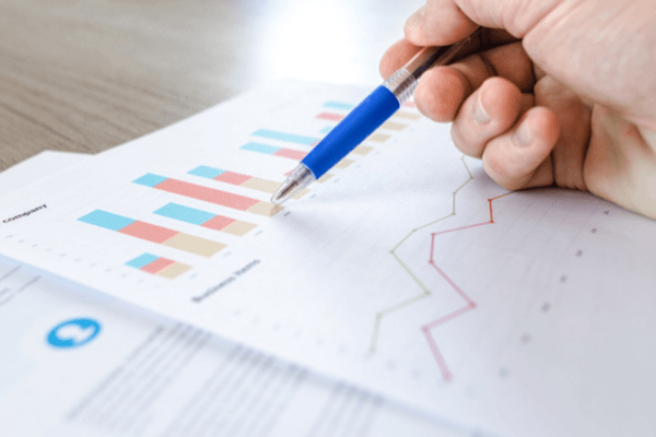 A man is point to bar graphs on a sheet of paper with his pen.