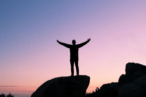 Silhouette of a man standing on a rock with his hands raise in the air.