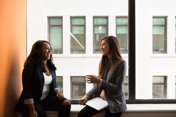 Two women are sat on a windowsill in a work environment talking and smiling