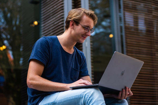 man holding a laptop outside an office showing remote working
