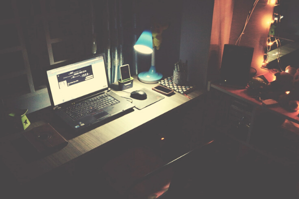 laptop and desk at nightime showing how people can work in their personal time.