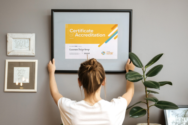 woman is hanging her Company Culture Accreditation on her office wall.