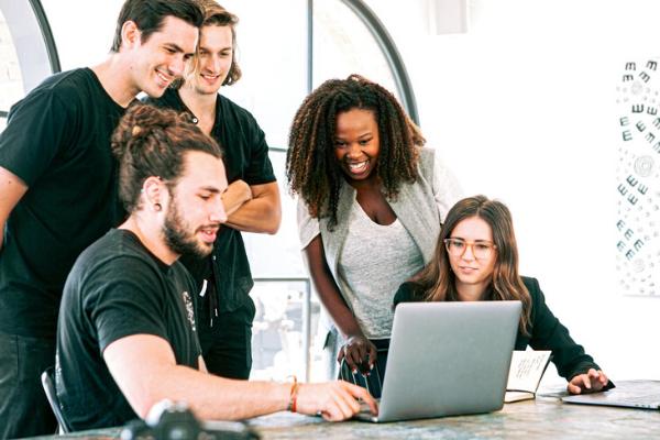 team are sat around computer smiling