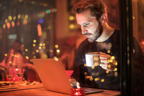 man sat in coffee shop on laptop at night time with drink in hand