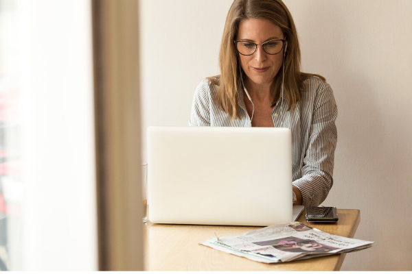 woman sat working on laptop with a newspaper next to her
