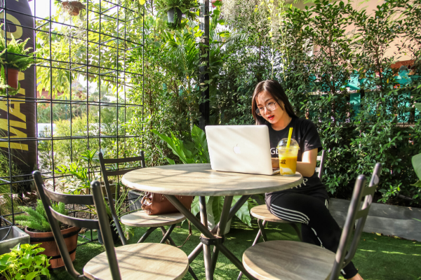 woman sat in garden on laptop