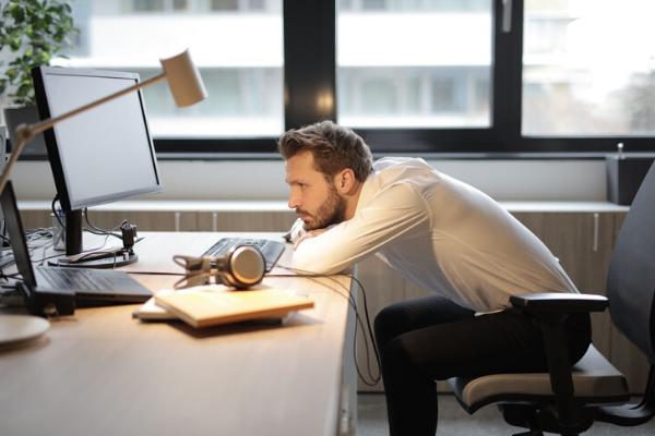 man slumped over his desk looking unhappy