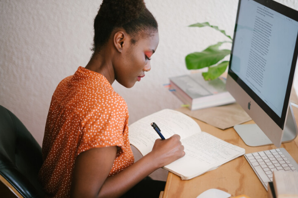 woman writing in notebook on her desk