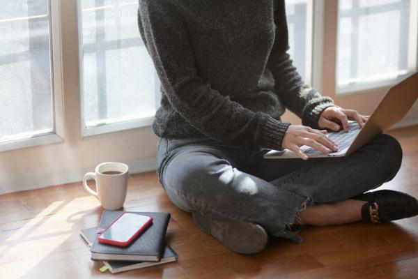 woman typing on laptop sat on the floor