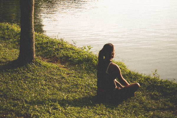 woman meditating on grass in front of a lake