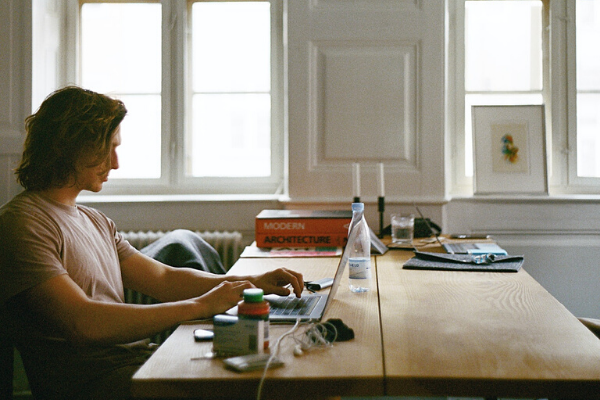 man sat at home remote working from laptop